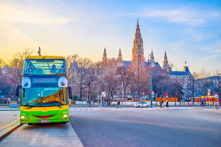 VIENNA, AUSTRIA - FEBRUARY 18, 2019: The funny double-decker sightseeing bus, parked next to one of the main landmarks of the city, the Rathausplatz with high City Hall building, on February 18 in Vienna.