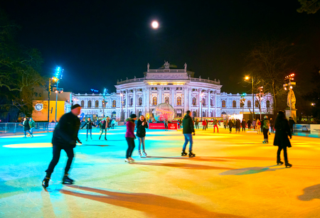 VIENNA, AUSTRIA - FEBRUARY 18, 2019: The locals ice skate on the large ice skating rink at Rathausplatz, that is one of the most favourite winter leisure event among youth, on February 18 in Vienna.