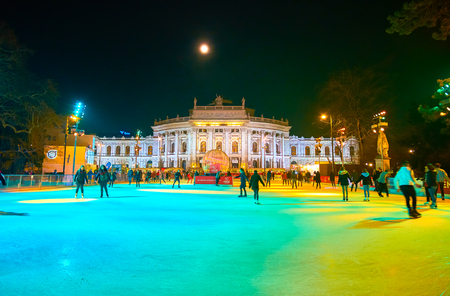 VIENNA, AUSTRIA - FEBRUARY 18, 2019: The large ice skating rink on Rathausplatz with view on Burgtheater on background, on February 18 in Vienna.