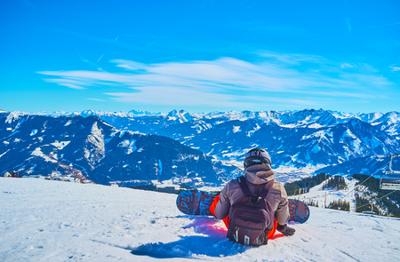 ZELL AM SEE, AUSTRIA - FEBRUARY 28, 2019: The snowboarder takes some rest, sitting on the snow and watching mountain scenery from the slope of Schmitten mount, on February 28 in Zell am See