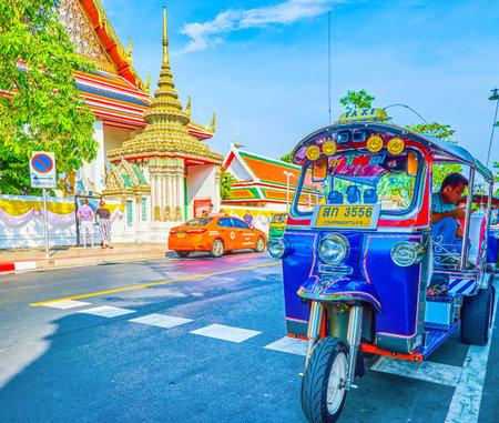 BANGKOK, THAILAND - APRIL 22, 2019: The large illuminated cruise ship sailing along Chao Phraya river passes by Wat Arun temple, on April 22 in Bangkok