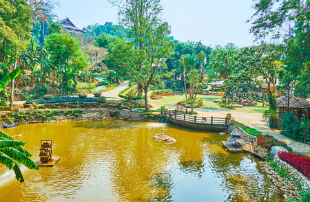 The perfectly landscaped Mae Fah Luang (Doi Tung) botanical garden with small lake, surrounded by lush green trees and flower beds, Chiang Rai, Thailand