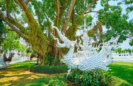 The white stucco statue of mythical half-elephant half-bird creature of hatsadiling (nok hatsadi, nok hat, hatsading) in shade of spreading tree in White Temple (Wat Rong Khun) garden, Chiang Rai, Thailand Editorial