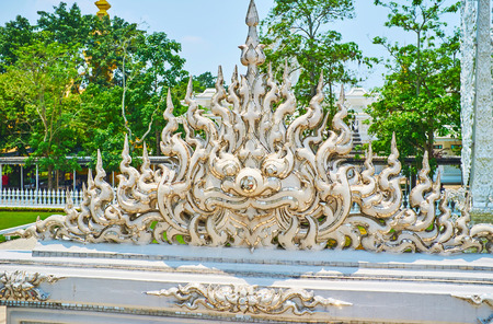 The stucco head of dragon, decorated with mirror details, located at the White Temple (Wat Rong Khun), Chiang Rai, Thailand Editorial