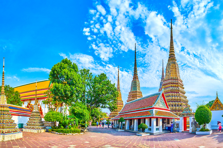 BANGKOK, THAILAND - APRIL 22, 2019: Panorama of Phra Maha Chedi shrine, that consists of large stupas, covered with colorful tiles, surrounded with walls with scenic gates, on April 22 in Bangkok