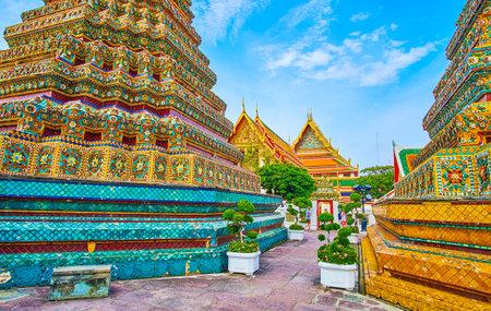 BANGKOK, THAILAND - 22. APRIL 2019: Der schmale Weg zwischen großen Stupas des Phra Maha Chedi-Schreins führt am 22. April in Bangkok zur Gasse des Wat Pho-Komplexes