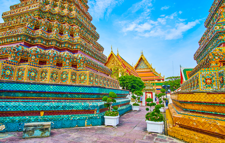 BANGKOK, THAILAND - APRIL 22, 2019: The narrow way between large stupas of Phra Maha Chedi shrine leads to the alley of Wat Pho complex, on April 22 in Bangkok