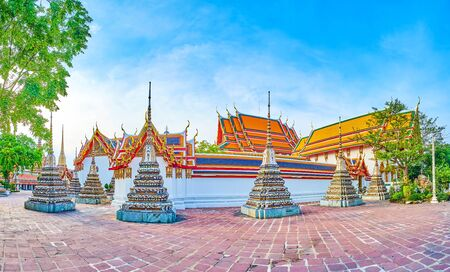 Panoramic view on outer side of walls of Phra Rabiang cloister with small chedis, that surround Prha Ubosot, the main shrine of Wat Pho temple complex in Bangkok, Thailand