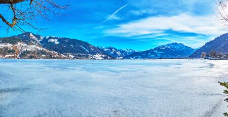 Winter panorama of Zeller see lake, covered with ice and snow and surrounded by Alpine ranges, Zell am See, Austria Stock Photo