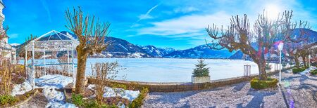Enjoy the sunny winter weather, walking along the bank of frozen Zeller see lake, observing topiary garden with vintage alcove and snowy Alps on background, Zell am See, Austria Stock Photo