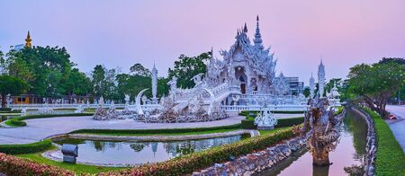 Evening is perfect time to explore unusual White Temple (Wat Rong Khun) with its ornate Ubosot, scary sculptures, intricate mirror decorations and topiary garden, Chiang Rai, Thailand 免版税图像