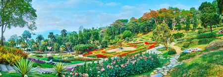 Panorama of Mae Fah Luang garden with picturesque flower beds, blooming flame trees, tall palms and topiary plants, Doi Tung, Thailand