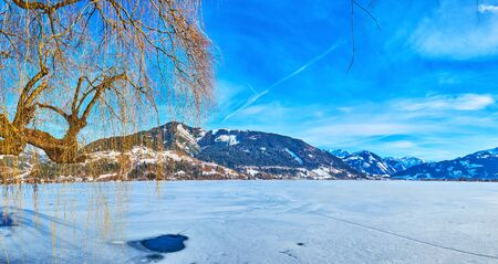 Panorama of frozen Zeller see lake with a view on small ice hole on the white surface, Alpine mountain range on background and weeping willow tree, Zell am See, Austria