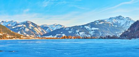 Walk along the Esplanade embankment of frozen Zeller see (lake) with a view on its bright blue surface, snowy Alps and trees of Elisabeth park, Zell am See, Austria Stock Photo