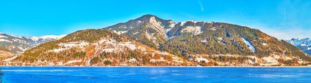 Panorama of the Alpine mountain range behind the blue icy surface of Zeller see lake, Zell am See, Austria
