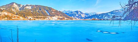 Enjoy the winter in Alps and observe the bright blue surface of Zeller see lake, covered with ice and snow crust, Zell am See, Austria Stock Photo