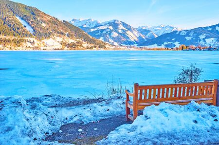The small wooden bench on snowy bank of frozen Zeller see lake, Elisabeth park, Zell am See, Austria Stock Photo