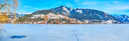 Panorama of winter Zeller see lake, covered with ice and snow crust , surrounded by mountains, Alpine villages and ski resorts, Zell am See, Austria