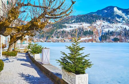 Enjoy the small lakeside garden, stretching along the bank of frozen Zeller See lake, with vintage lanterns, small spruces, topiary bushes and spread trees, Zell am See, Austria