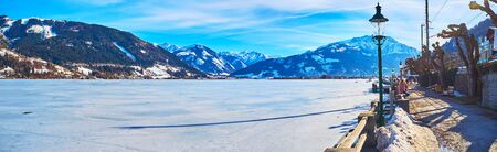 Enjoy the lakeside Elisabeth park with a view on Zeller see, covered with ice and surrounded by rocky Alps, Zell am See, Austria. Stock Photo