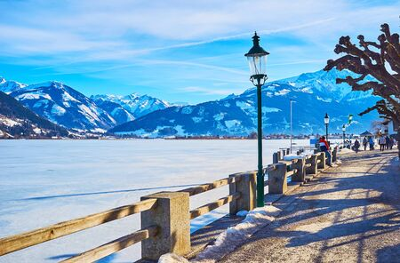 Walk winter Elisabeth park and watch the frozen surface of Zeller see lake, vintage streetlights and Alpine landscape on background, Zell am See, Austria