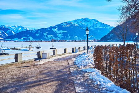 Winter is perfect season to visit Zell am See, enjoy the ski resort of Schmitten mountain, walk by the frozen Zeller See lake and observe Alpine landscapes, covered with snow, Austria Stock Photo