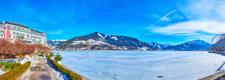 ZELL AM SEE, AUSTRIA - FEBRUARY 28, 2019: Panorama from embankment of Elisabeth park with a view on Zeller see, covered with ice, Alps and Grand Hotel on the lakes bank, on February 28 in Zell Am See Editorial