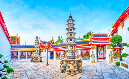 BANGKOK, THAILAND - APRIL 22, 2019: The small yard of Phra Rabiang cloister with gilden Buddhas in covered gallery and two stone towers in the middle, on April 22 in Bangkok Editorial
