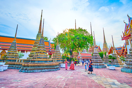 BANGKOK, THAILAND - APRIL 22, 2019: The tourists walk in Wat Pho temple overlooking magnificent architecture of the surriunding shrines, on April 22 in Bangkok Editorial