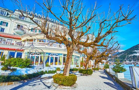 ZELL AM SEE, AUSTRIA - FEBRUARY 28, 2019: The classic building of Grand Hotel is decorated with small topiary garden, facing Zeller See lake, on February 28 in Zell Am See