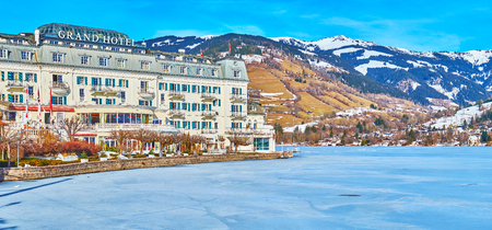 ZELL AM SEE, AUSTRIA - FEBRUARY 28, 2019: The luxury Grand Hotel, located on the bank of frozen Zeller See lake with scenic mountain range on background, on February 28 in Zell Am See