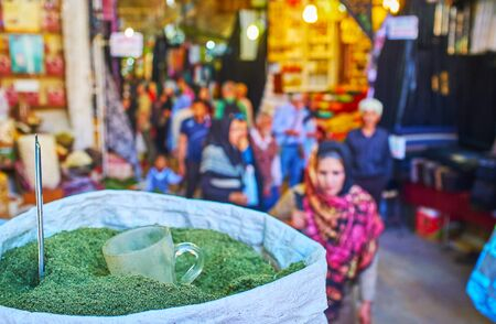 SHIRAZ, IRAN - OCTOBER 14, 2017: The crowded alleyway of historical Vakil Bazaar with a view on the bag of dried pennyroyal herb on the foreground, on October 14 in Shiraz.