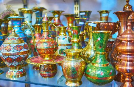 The ornate tableware of Meenakari decorative technique; jugs and coffee pots are covered with engravings and colored enamels, Shiraz, Iran