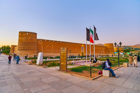 SHIRAZ, IRAN - OCTOBER 14, 2017: Evening walk around Shohada Square with a view on medieval Karim Khan citadel with brick leaning towers, on October 14 in Shiraz.
