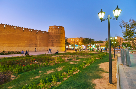 SHIRAZ, IRAN - OCTOBER 14, 2017: Shohada square is covered with flower beds and trees, surronding its main landmark - medieval Karim Khan citadel, on October 14 in Shiraz.