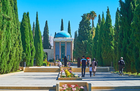 SHIRAZ, IRAN - OCTOBER 14, 2017: People walk the cypress alley of Tomb Saadi (Mausoleum of Sa'di, Sadiyeh) with flower bed amid the way and richly decorated pavilion on background, on October 14 in Shiraz