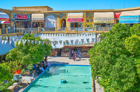 SHIRAZ, IRAN - OCTOBER 14, 2017: The scenic area of Saraye Moshir Bazaar with fountain in the middle, shady trees with banches and multiple stores around small garden, on October 14 in Shiraz. Editoriali