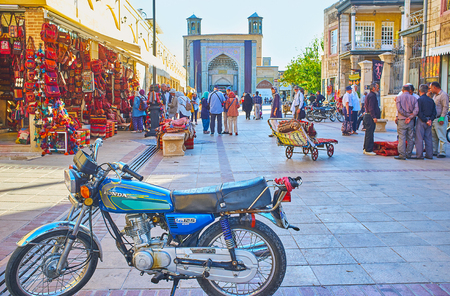 SHIRAZ, IRAN - OCTOBER 14, 2017: The busy street of Vakil Bazaar with a view on parked vintage bike, stalls and stores of Vakil Bazaar, walking people and portal of Vakil mosque on background, on October 14 in Shiraz