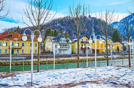 The view from the snowy Esplanade park on the Traun river, old houses of Bad Ischl and Siriuskogl mountain on the background, Austria