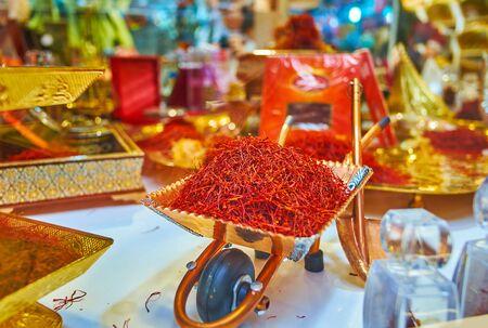 The small copper souvenir wheelbarrow, loaded with dried saffron stigmas in showcase of spice shop of Tajrish Bazaar, Tehran, Iran Imagens