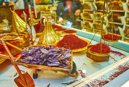 The different souvenir tableware and spice storages of brass and copper with red stigmas of saffron and the souvenir wheelbarrow, full of dried saffron flowers, Tajrish Bazaar, Tehran, Iran