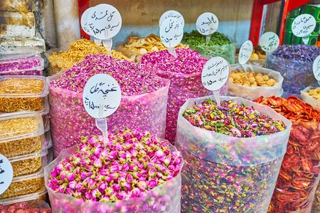 The large plastic bags with dried rose flowers, petals, flower tea mixes, nuts, fruits and other herbs and spices with Iranian price boards in store of Tajrish Bazaar, Tehran, Iran Stock Photo