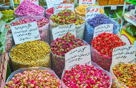 Dried rose flowers of many species in bags with boards, containing information about the name of product, recipe of tea beverage, price and properties in Persian language, Tajrish Bazaar, Tehran, Iran