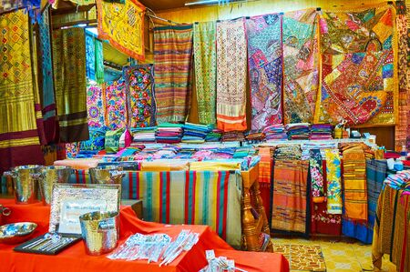 The stall of Kalare Night Market with wide range of colorful fabrics of cotton, silk and synthetic materials, decorated with prints, embroideries, patchwork and patterns,  Chiang Mai, Thailand