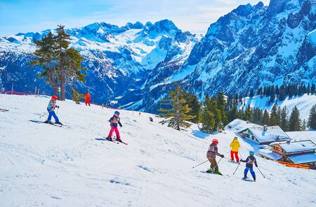 GOSAU, AUSTRIA - FEBRUARY 26, 2019: The group of youngest beginner skiers makes the downhill from the Zwieselalm mountain of Dachstein West Alps, on February 26 in Gosau.