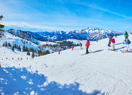 GOSAU, AUSTRIA - FEBRUARY 26, 2019:  The sportsmen on the ski run on gentle slope of Zwieselalm mount in Dachstein West Alps, on February 26 in Gosau.