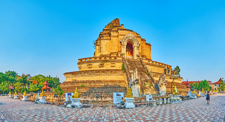 CHIANG MAI, THAILAND - MAY 2, 2019: The ruins of extant Phra That Chedi Luang of Wat Chedi Luang complex with huge Naga serpents and replicas of gilt chedis and Burmese stupas on foreground, on May 2 in Chiang Mai