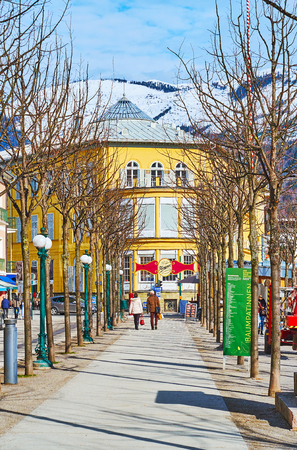 BAD ISCHL, AUSTRIA - FEBRUARY 26, 2019: Walk the alley of winter Esplanade park, lined with trees and vintage streetlights, on February 26 in Bad Ischl.