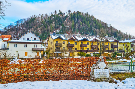 BAD ISCHL, AUSTRIA - FEBRUARY 26, 2019: Memorial stone of Franz Stelzhamer on the bank of Traun river in Sissi Park; the Siriuskogl mount, topped with tower, is seen on background, on February 26 in Bad Ischl.