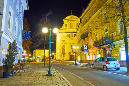 BAD ISCHL, AUSTRIA - FEBRUARY 20, 2019: Evening Franz Joseph Strasse with a view on illuminated St Nicholas Parish Church and classical buildings, on February 20 in Bad Ischl